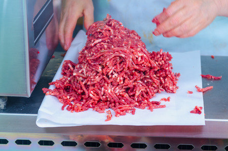 Butcher prepares minced meat in the market. Butchery concept photo