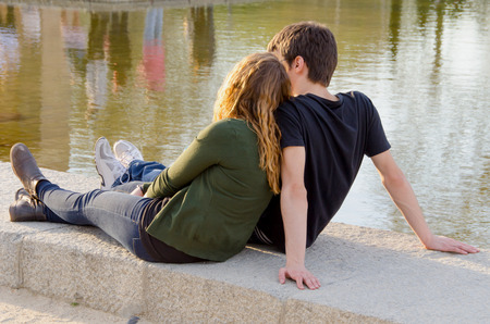 sitting on the ground: Young couple of lovers sitting in the ground of the park