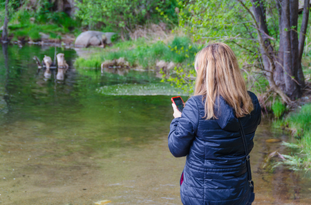 coverage: Woman searching network coverage in a river