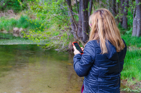 coverage: Woman searching network coverage near a river. Connectivity and telecommunications concept Stock Photo