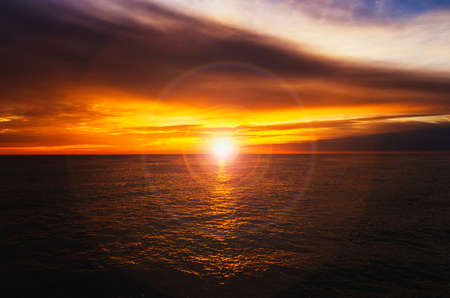 Very beautiful sunset at sea in yellow with a lens flare effect photo