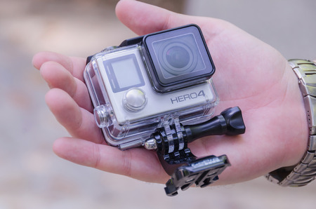 cam gear: LEGANES, MADRID, SPAIN - JULY 4, 2015: A man holding Gopro Hero 4. Go pro Hero 4 is a compact, lightweight personal camera for taking action video and photography