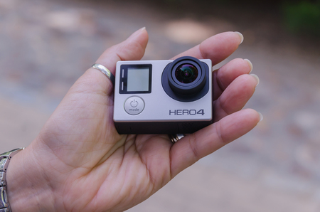 pro: LEGANES, MADRID, SPAIN - JULY 4, 2015: A woman holding Gopro Hero 4. Go pro Hero 4 is a compact, lightweight personal camera for taking action video and photography