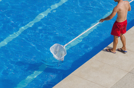 pool side: A man cleans the swimming pool. Summer maintenance service