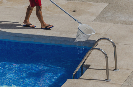 pool stick: Pool cleaner using an stick with a net to clean the swimming pool