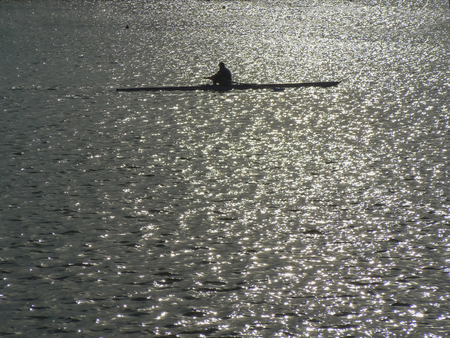 rower: A rower in a lake at sunset Stock Photo