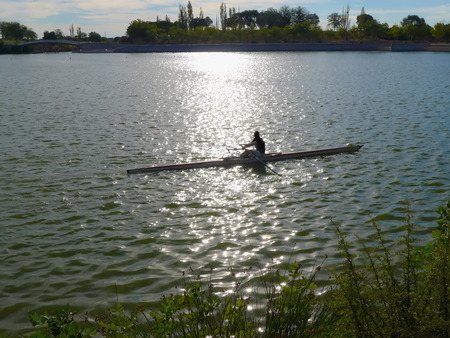 rower: A rower training in a lake at sunset Stock Photo