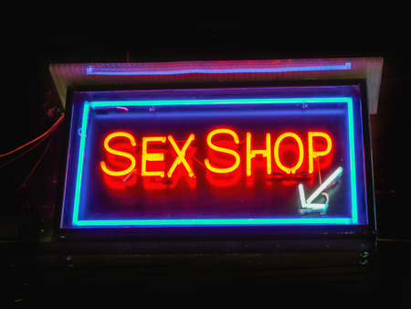 sex: Red neon sex shop sign indicates the entrance at the shop Stockfoto