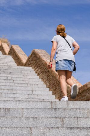 mini: An adult woman wearing miniskirt walks up the stairs with an smartphone Stock Photo