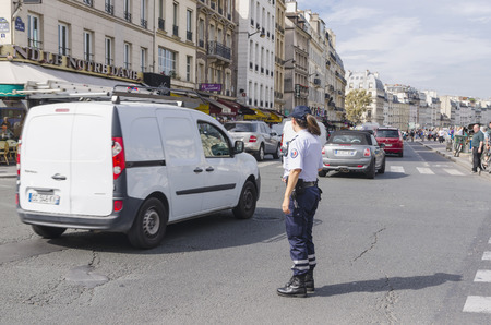 femme policier: PARIS, FRANCE - 17 septembre 2014: La policière dans les rues de Paris. La police nationale est le principal organisme d'application de la loi civile de la France.