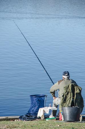 recreational sport: Fisherman fishing in a calm lake. Fishing is also a recreational sport Stock Photo