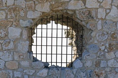 slavery: Jail. Grilled hole in the wall of a prison. Slavery, punishment and prevention