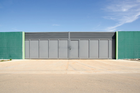 closed society: Modern metal gates painted in gray. Property entrance.