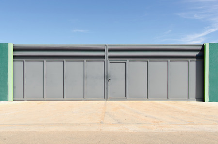 closed society: Modern metallic gate painted in gray. Porperty access closed