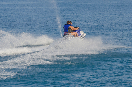 jet skier: A couple is riding a modern jet ski. Personal watercraft