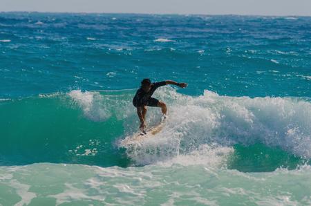 shorebreak: A man surfing over the waves in mediterranean sea