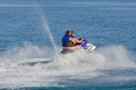 personal watercraft: A couple riding a personal watercraft in the mediterranean sea. jet ski Stock Photo