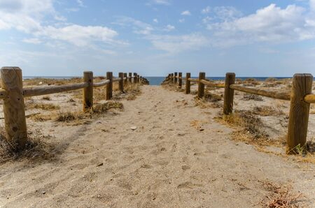 sandy beach: path to te beachwith wooden fences in Cabo de Gata, Almeria, Andalusia, Spain