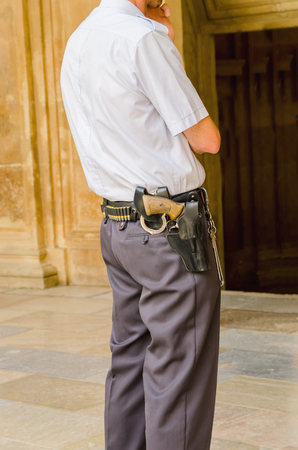 security uniform: Security guard standing and armed with shackles, a gun and bullets