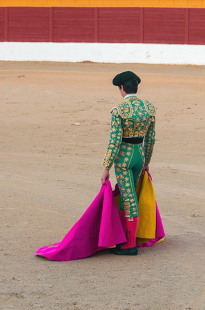 corrida: Standing torero dressed with a gold and green costume. Spanish corrida de toros