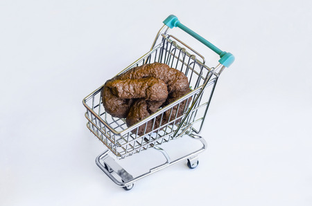 shit: Supermarket cart with a shit. Concept of consumerism and commercial abuse