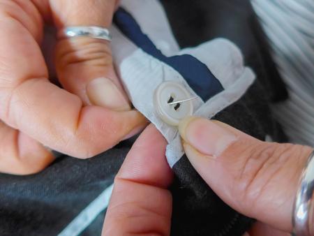 coser: Dos manos de coser un botón con una aguja