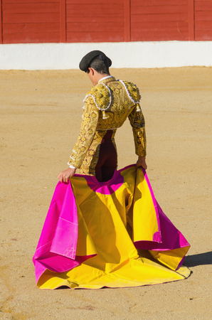 bull fight: bullfighter standing and holding the capote. Matador in the bullring