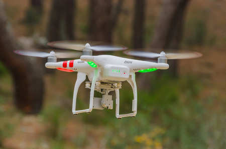 A drone equiped with four rotors and a camera is flying and taking pictures Archivio Fotografico