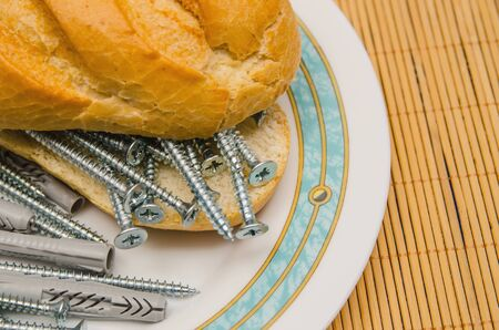 uneatable: Close-up of bread with nails and dowels on plate. Uneatable sandwich Stock Photo