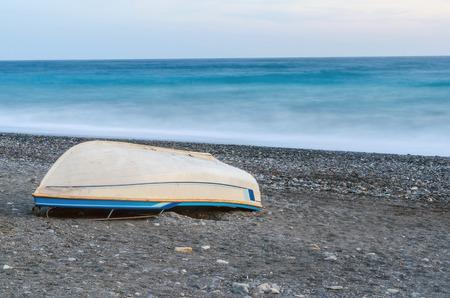 cabeza abajo: Barco al revés acostado en la playa de guijarros. foto La exposición a largo