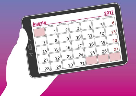 tablet pc in hand: august 2017, agosto 2017. A hand holds a tablet pc with a calendar sheet in spanish.
