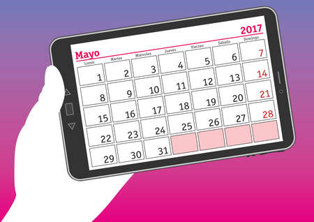 tablet pc in hand: May 2017, mayo 2017. A hand holds a tablet pc with a calendar sheet in spanish.