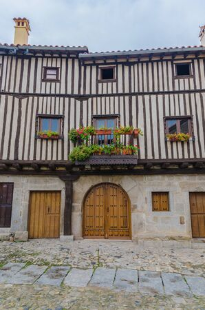 castile leon: View on house facade in La Alberca, Salamanca, Castile and Leon, Spain. Balcony decorated with flowers. Striped facade.