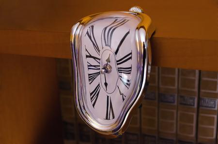 liquefied: Liquefied clock flowing down table. Roman numerals. surrealism
