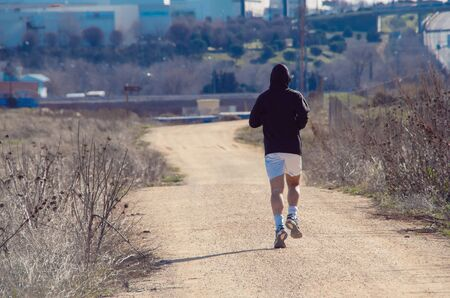 destinations: Unrecognizable man running down the road in countryside in sunlight