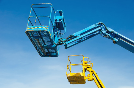 erector: Two cranes baskets against clear sky. Lifters in blue and yellow