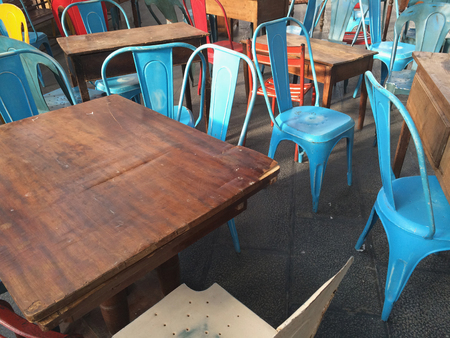 disordered: Empty blue metal chairs and wooden tables. Disordered furniture Stock Photo