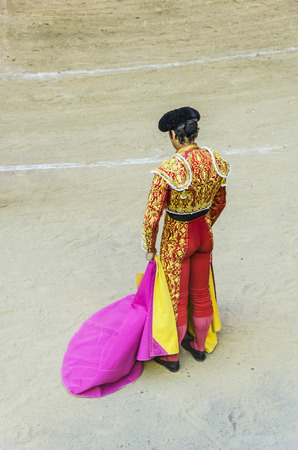 corrida: A bullfighter with red and gold costume awaiting for the bull in the bullring. Corrida de toros