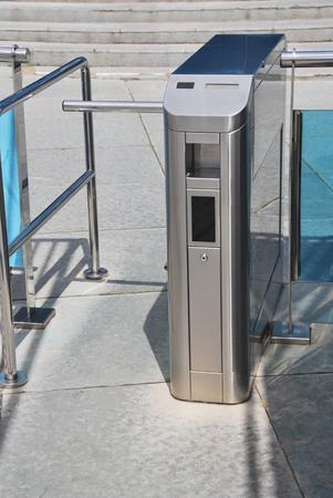 tourniquet: Close-up of metal turnstile closed on cement tiled floor. Modern tourniquet