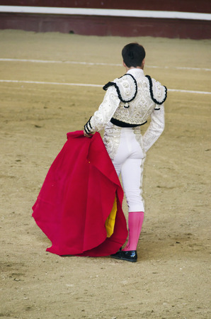 corrida: A bullfighter in white costume awaiting for the bull in the bullring. Corrida de toros.