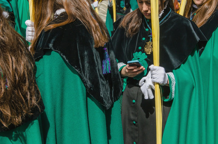 christianity palm sunday: VALLADOLID, SPAIN - MARCH 29, 2015: A girl member of a brotherhood holds her mobile phone during a procession in the spanish sacred week