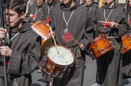 holy week: VALLADOLID, SPAIN - MARCH 29, 2015: Members of a brotherhood marching and playing drums in a Holy week procession