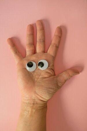 unrecognizable: Someones hand with toy eyes on it on pink background. Unrecognizable.