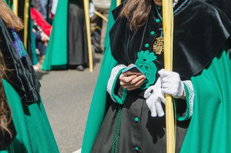 christianity palm sunday: A girl member of a brotherhood holding her mobile phone during a procession in the spanish sacred week Stock Photo