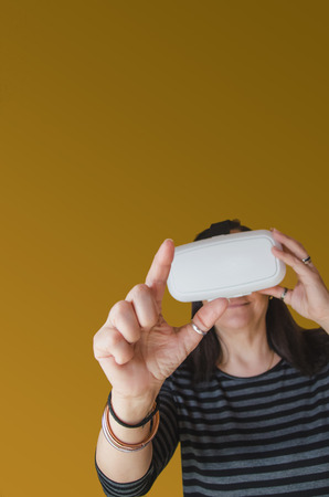 stereoscopic: A woman on brown background touch something while enjoying a 3d experience at home with a vr headset. Virtual reality gadget to use with a mobile phone and stereoscopic glasses
