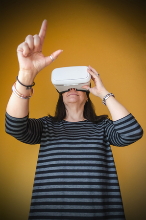 stereoscopic: A woman touch something while enjoying a 3d experience at home with a vr headset. Virtual reality gadget to use with a mobile phone and stereoscopic glasses