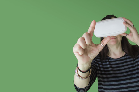 stereoscopic: A woman on green background touching something while enjoying a 3d experience at home with a vr headset. Virtual reality gadget to use with a mobile phone and stereoscopic glasses