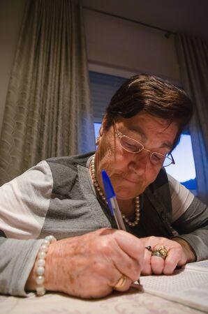 persona mayor: mujer de pelo negro con gafas haciendo el crucigrama mientras está sentado en la mesa Foto de archivo