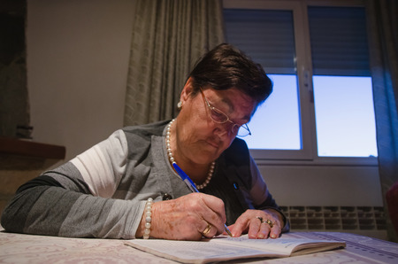 elderly woman: Leisure at home. Black haired woman in spectacles doing crossword puzzle while sitting at table.