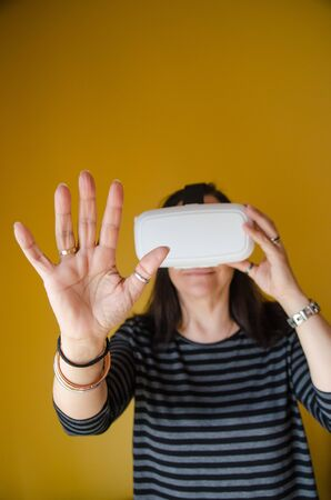 from below: Close-up of smiling woman using modern virtual reality glasses. Yellow wall on background. From below